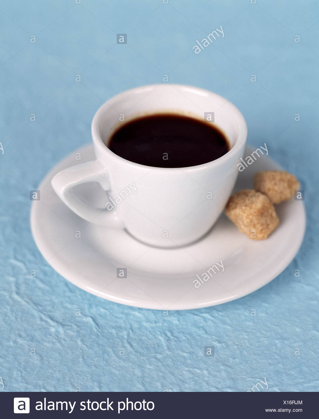 Expresso coffee in white expresso cup two brown sugar cubes in the 1058x1390