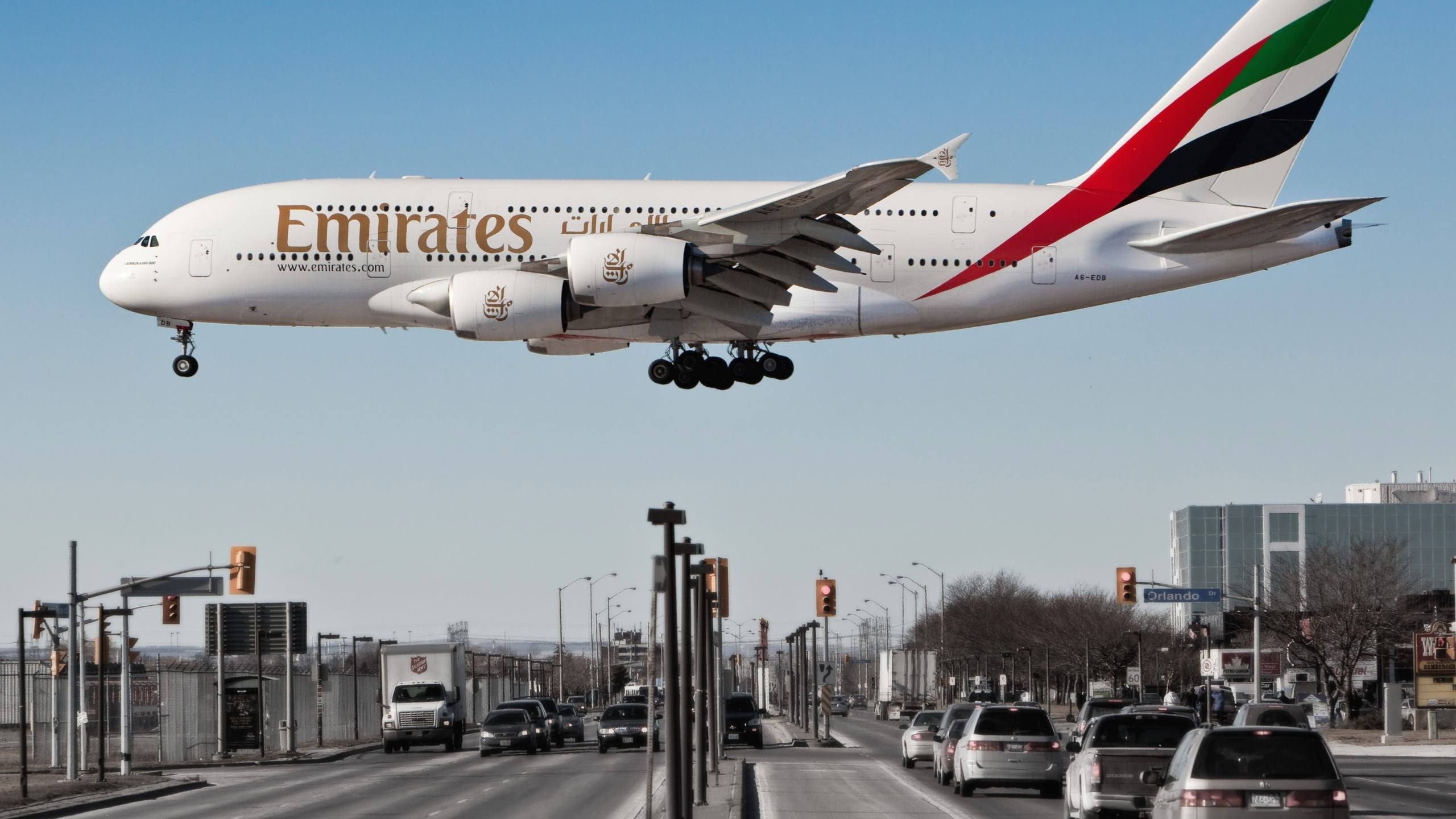 White Emirates plane below cars on road at daytime HD wallpaper 2560x1440