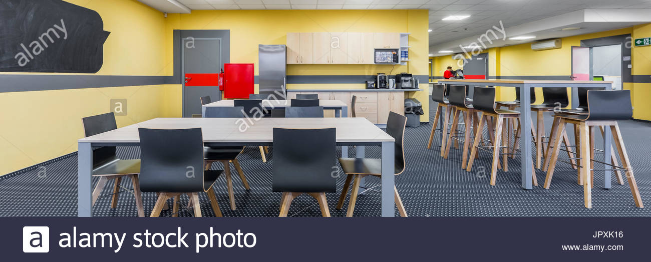 Panorama of modern lunchroom interior with wooden tables and black 1300x523