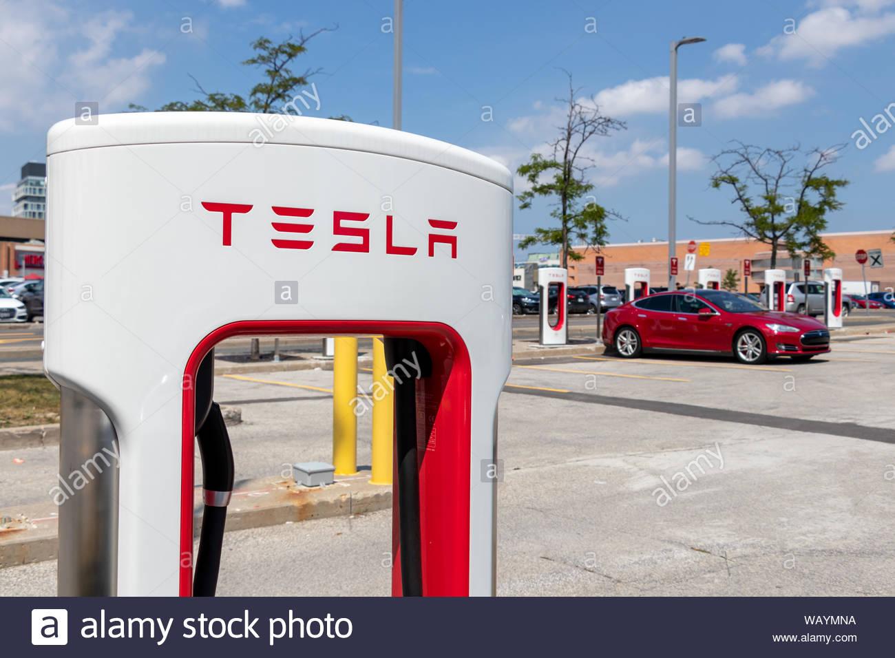 Tesla text logo atop of Tesla Supercharger Stall with red Tesla 1300x956