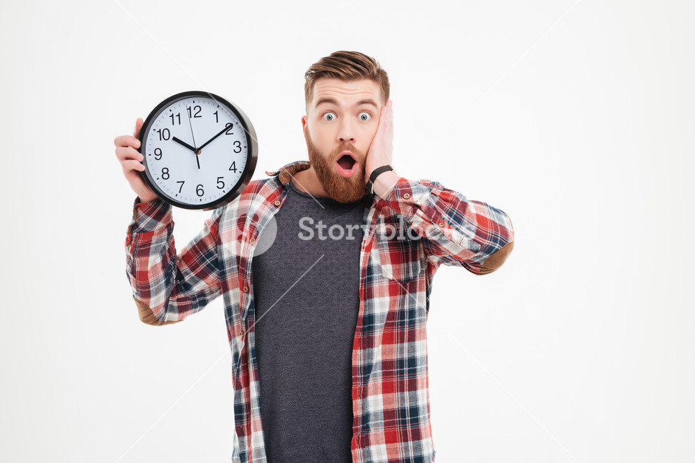 Surprised shocked young man in plaid shirt holding wall clock over 1000x667