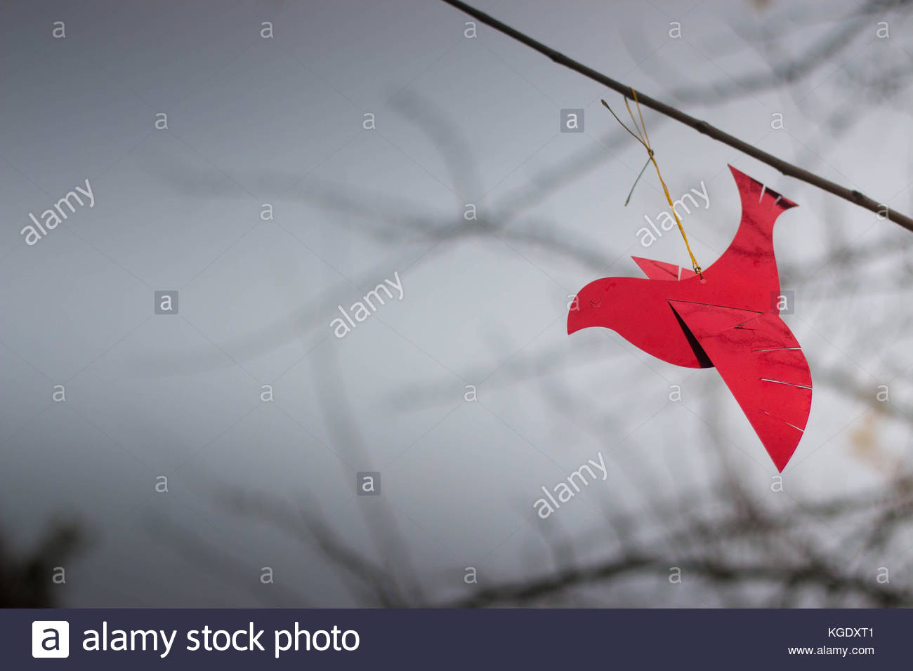 Shiny red bird ornament on a branch with cold winter sky in the 1300x956