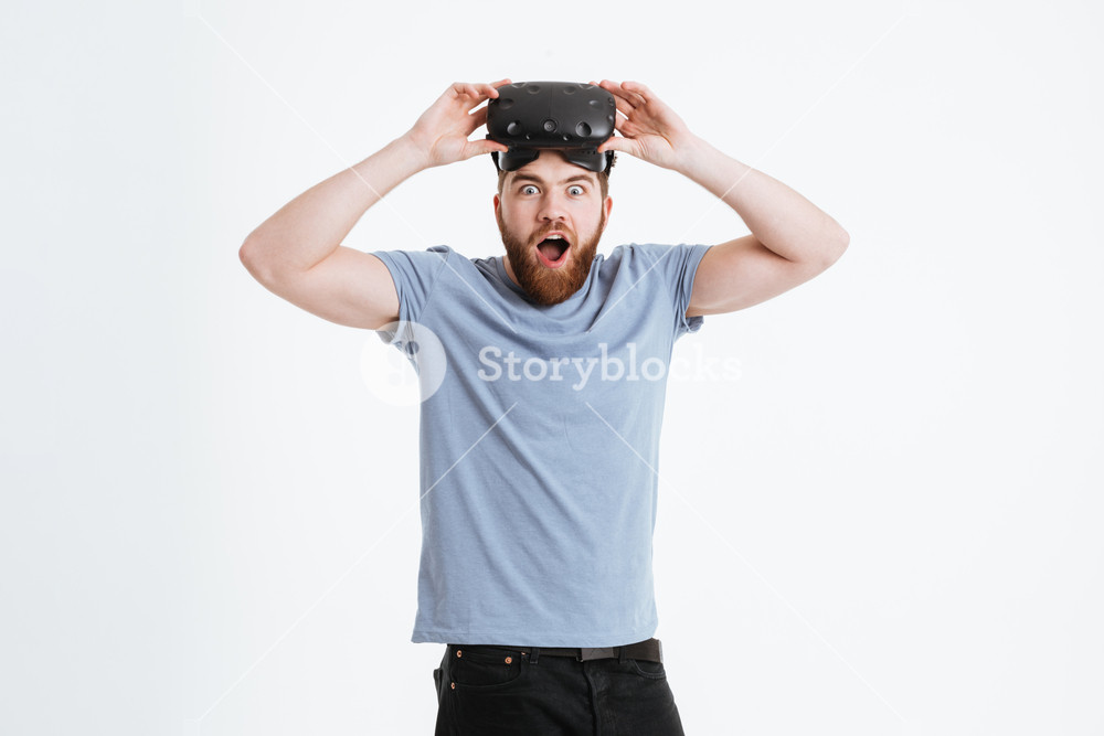 Photo of young shocked bearded man wearing virtual reality device 1000x667