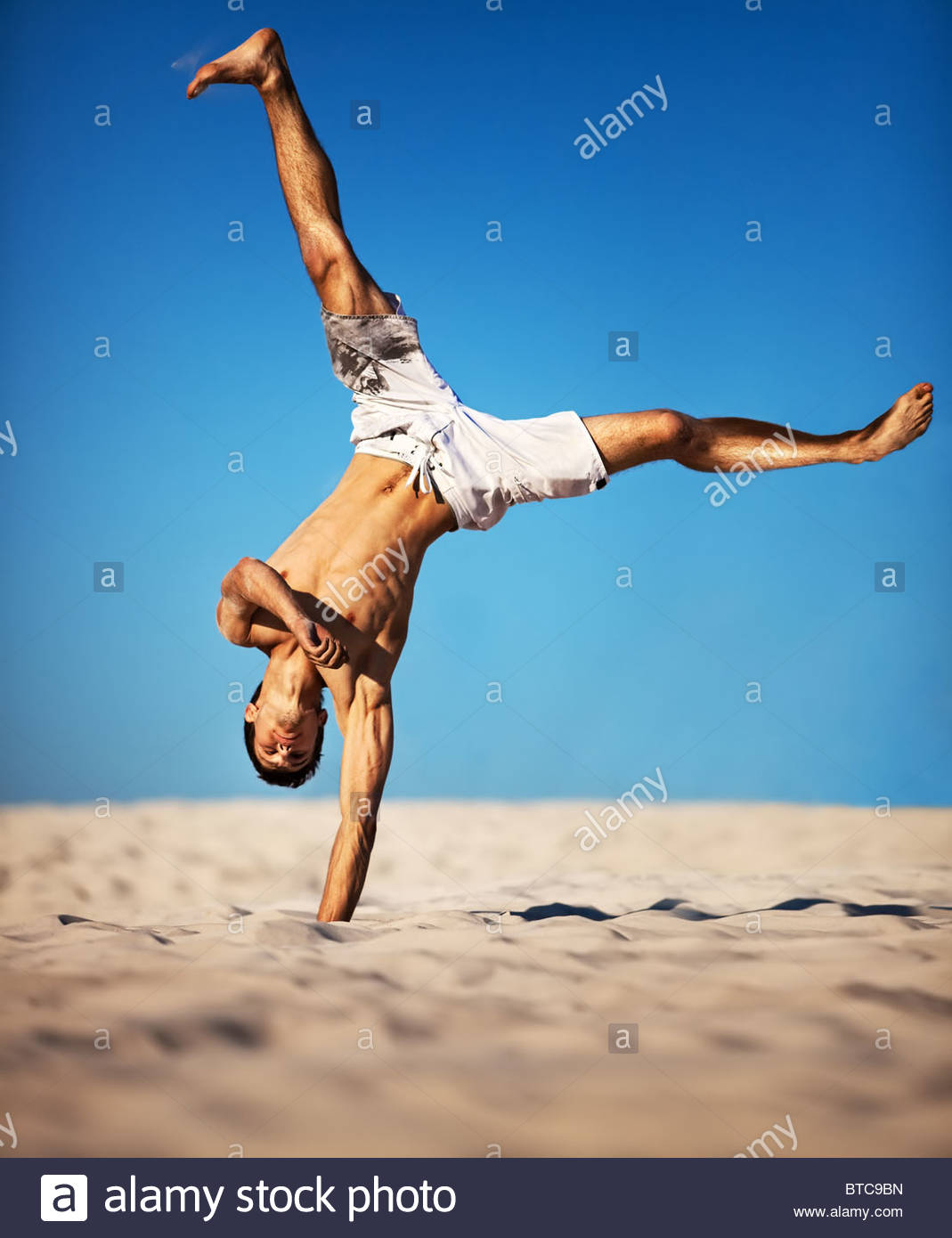 Young sportsman on beach On blue sky background Stock Photo 1069x1390