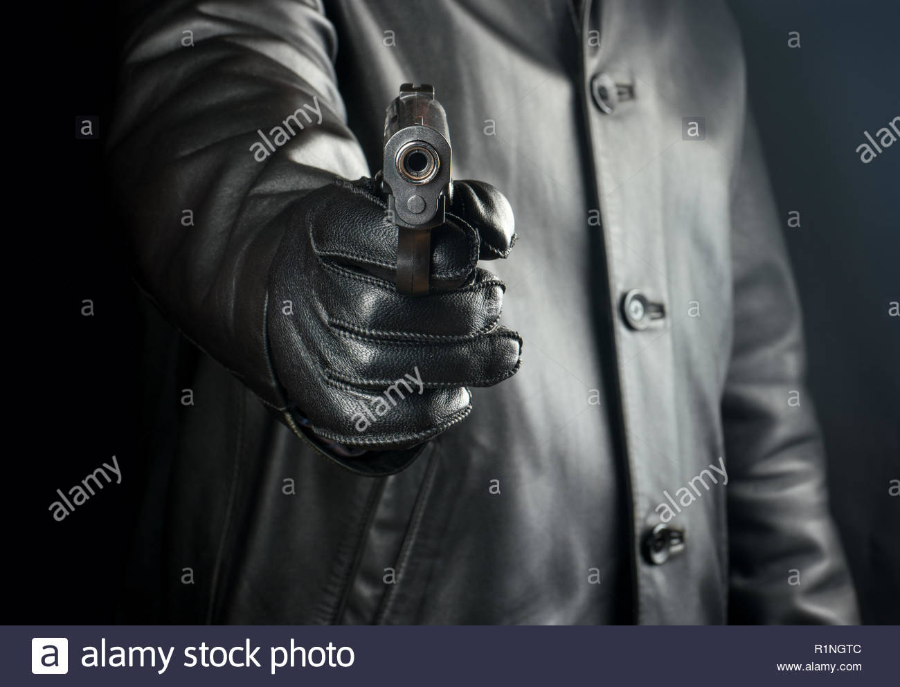 Bandit directs gun on black background closeup Stock Photo 1300x993