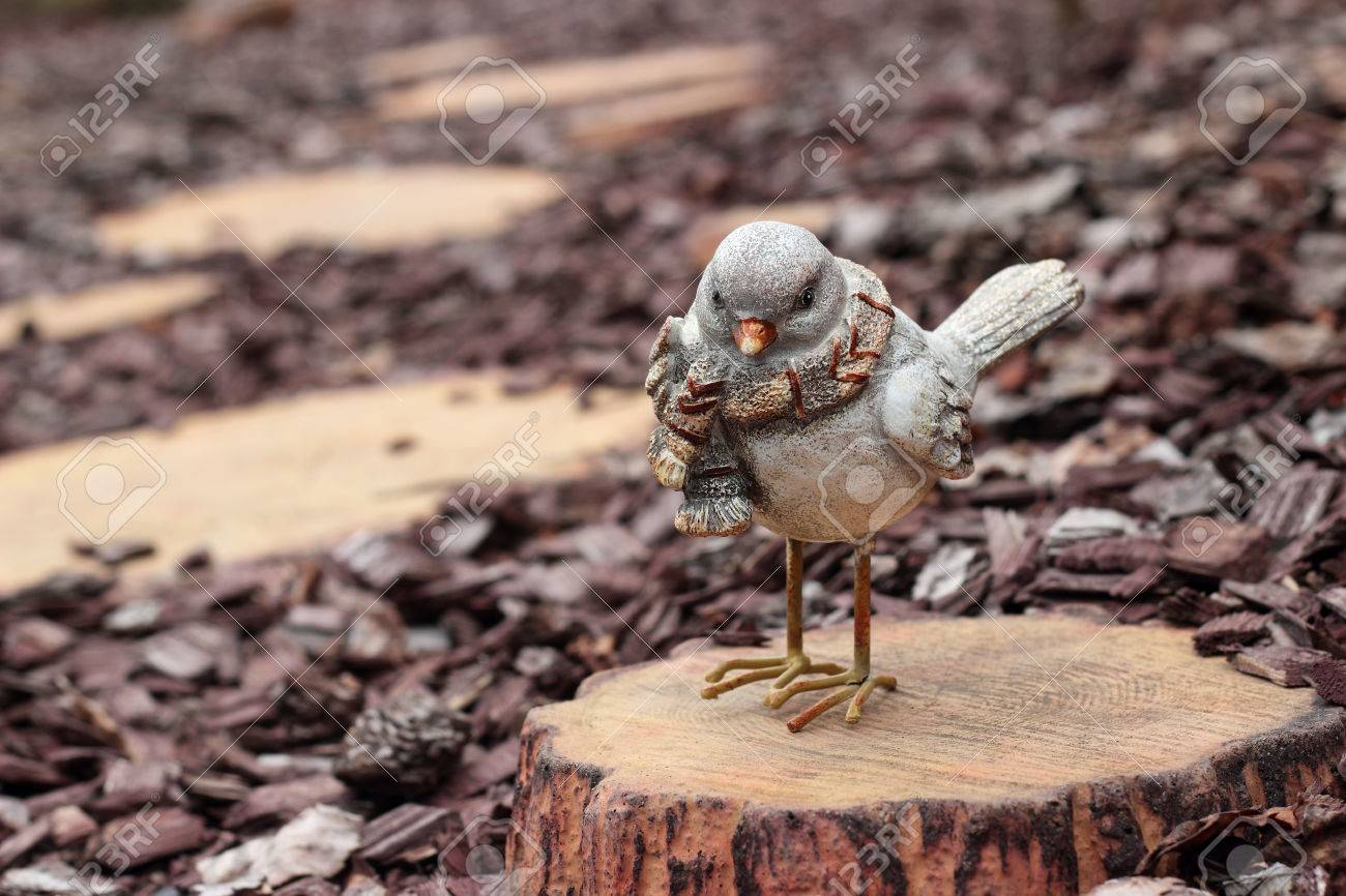Figurines   Bird On A Stub On A Wooden Stub Background Stock Photo 1300x866