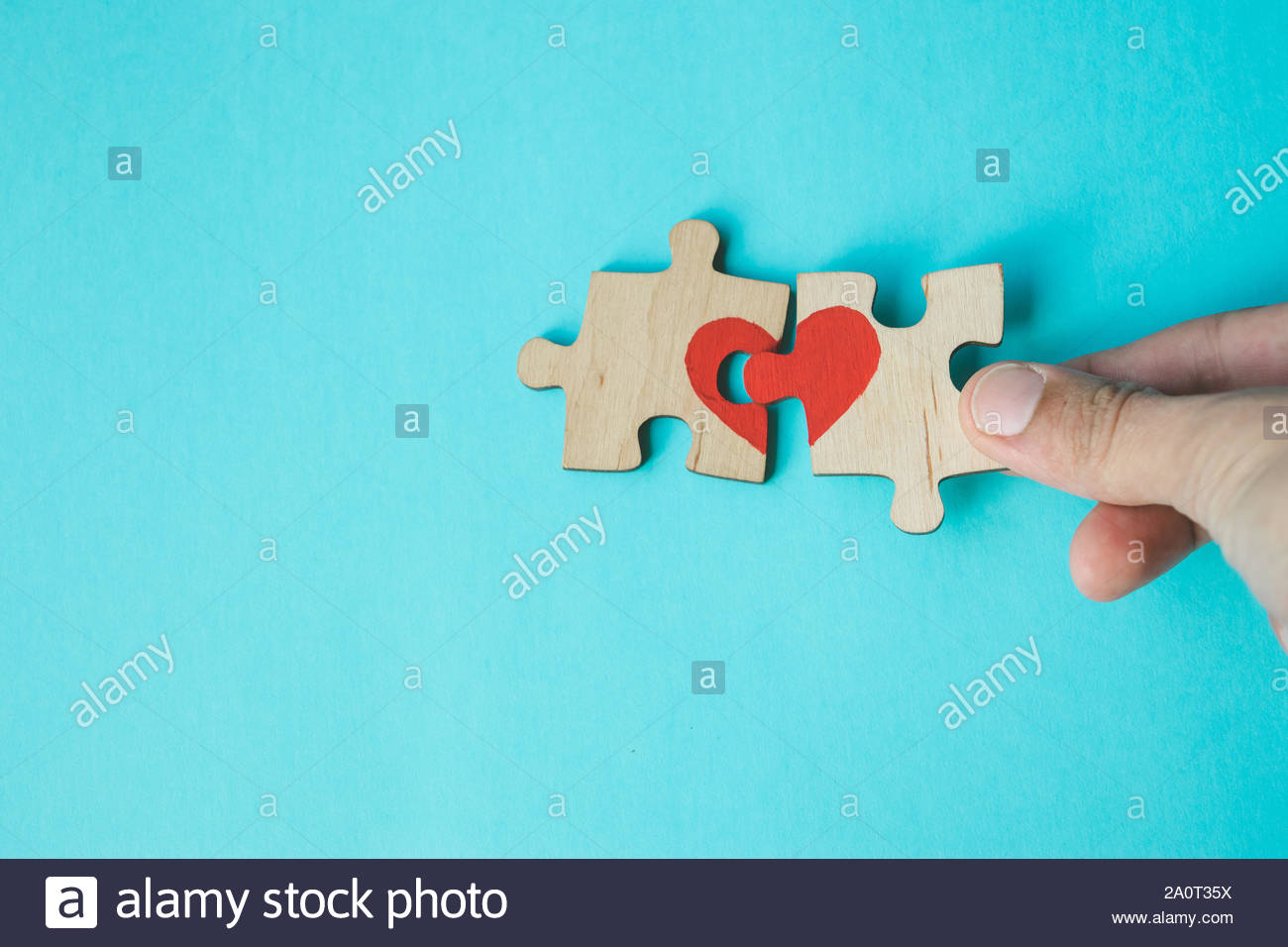 Female hand connecting puzzle with drawn red heart on blue 1300x956