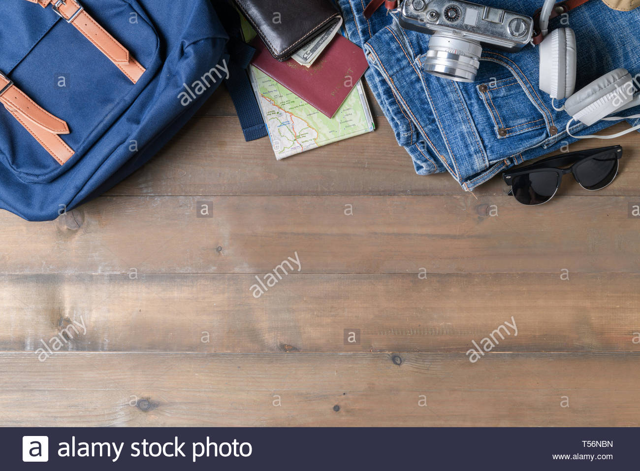 prepare backpack accessories and travel items on wood background 1300x956