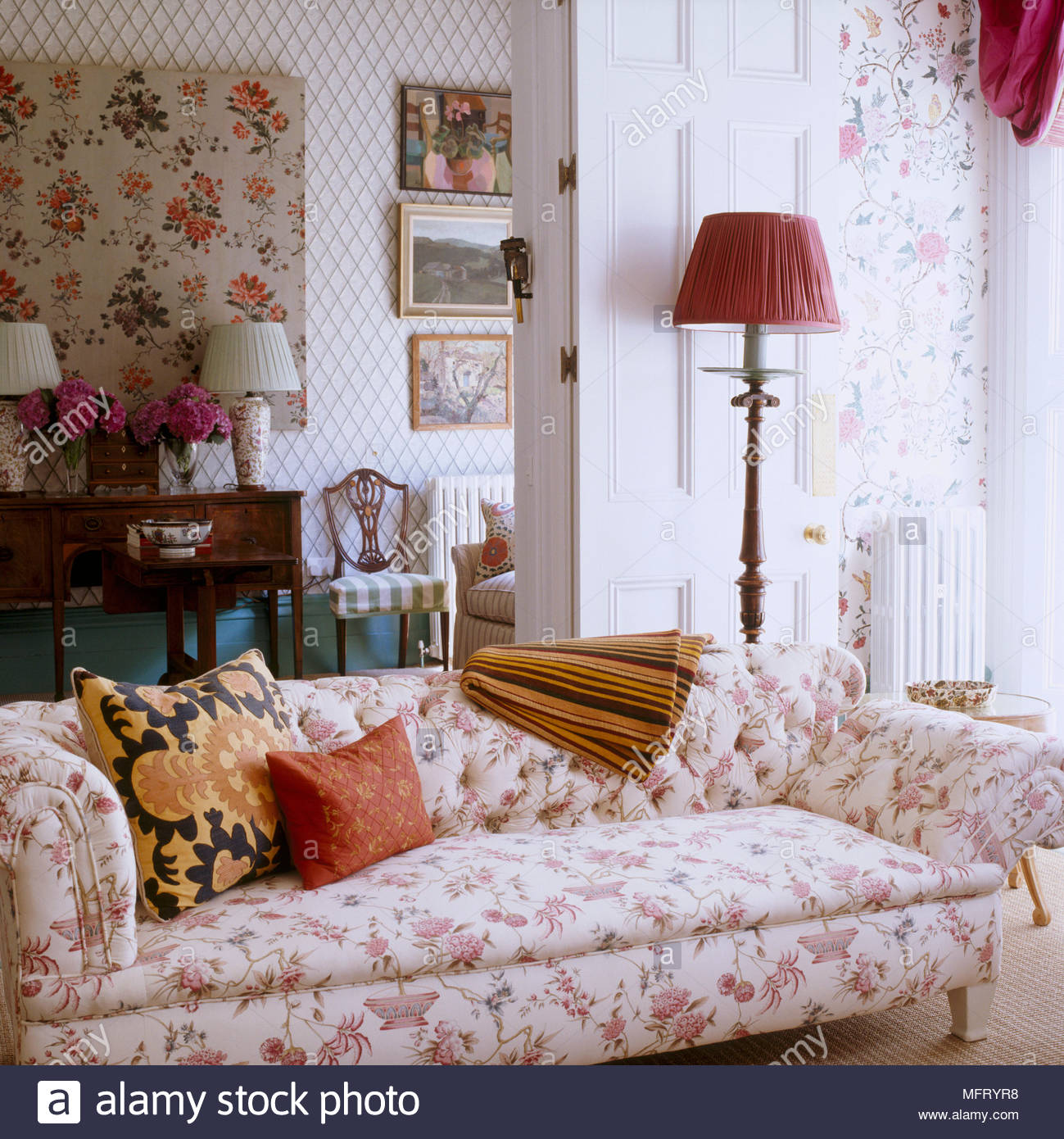 Sitting room with pink floral wallpaper upholstered sofa lamps 1299x1390