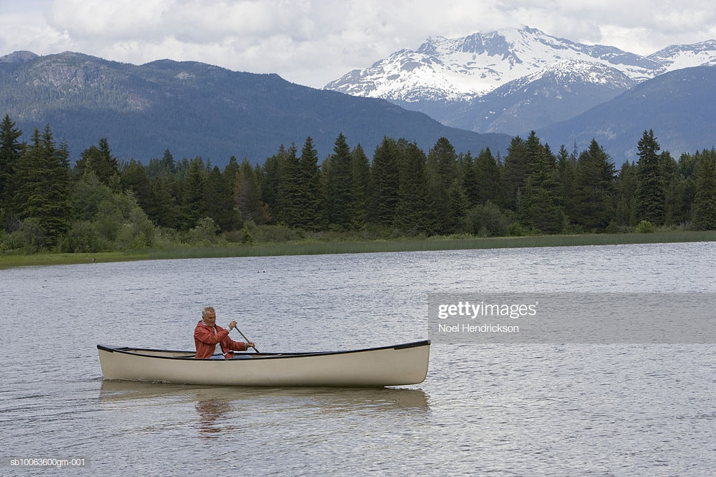 Senior Man In Canoe On River Mountain Range In Background High Res 1024x683