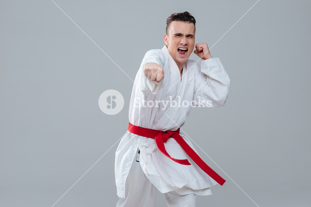 Image of handsome sportsman in kimono practicing at karate while 1000x667