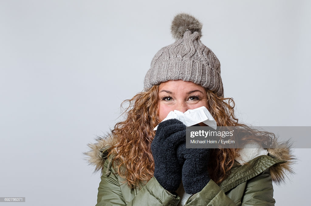 Portrait Of Young Woman Holding Handkerchief And Sneezing Against 1024x679