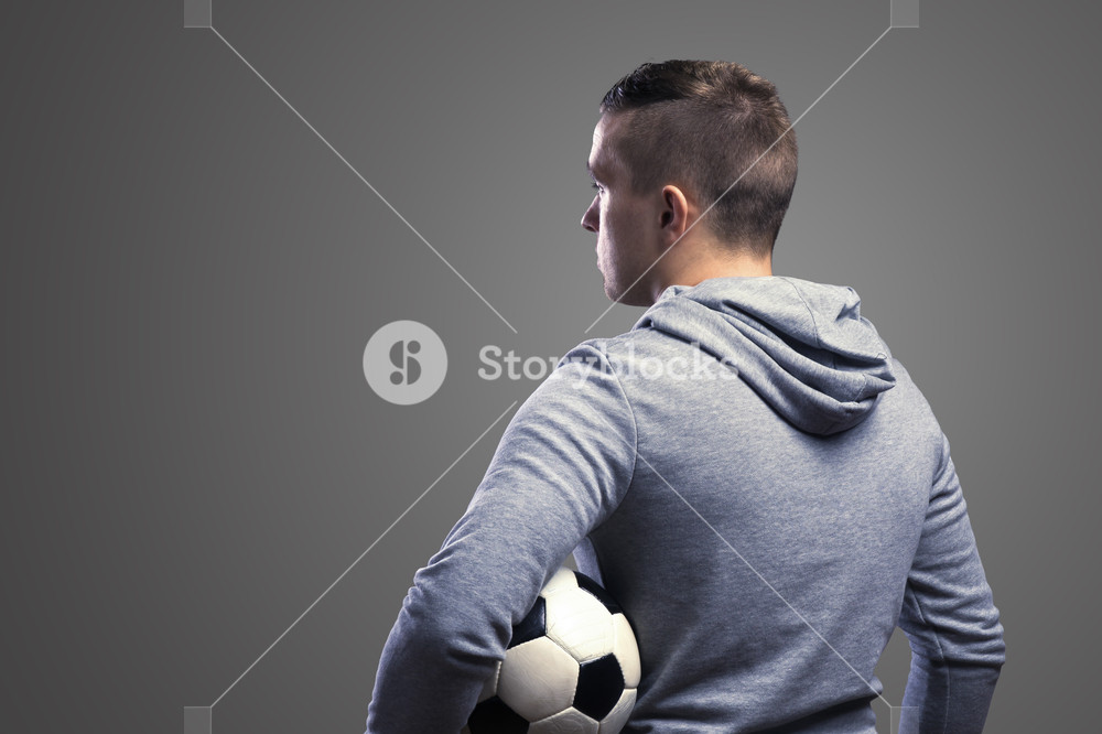 Young sportsman holding a soccer ball Studio shot on gray 1000x666