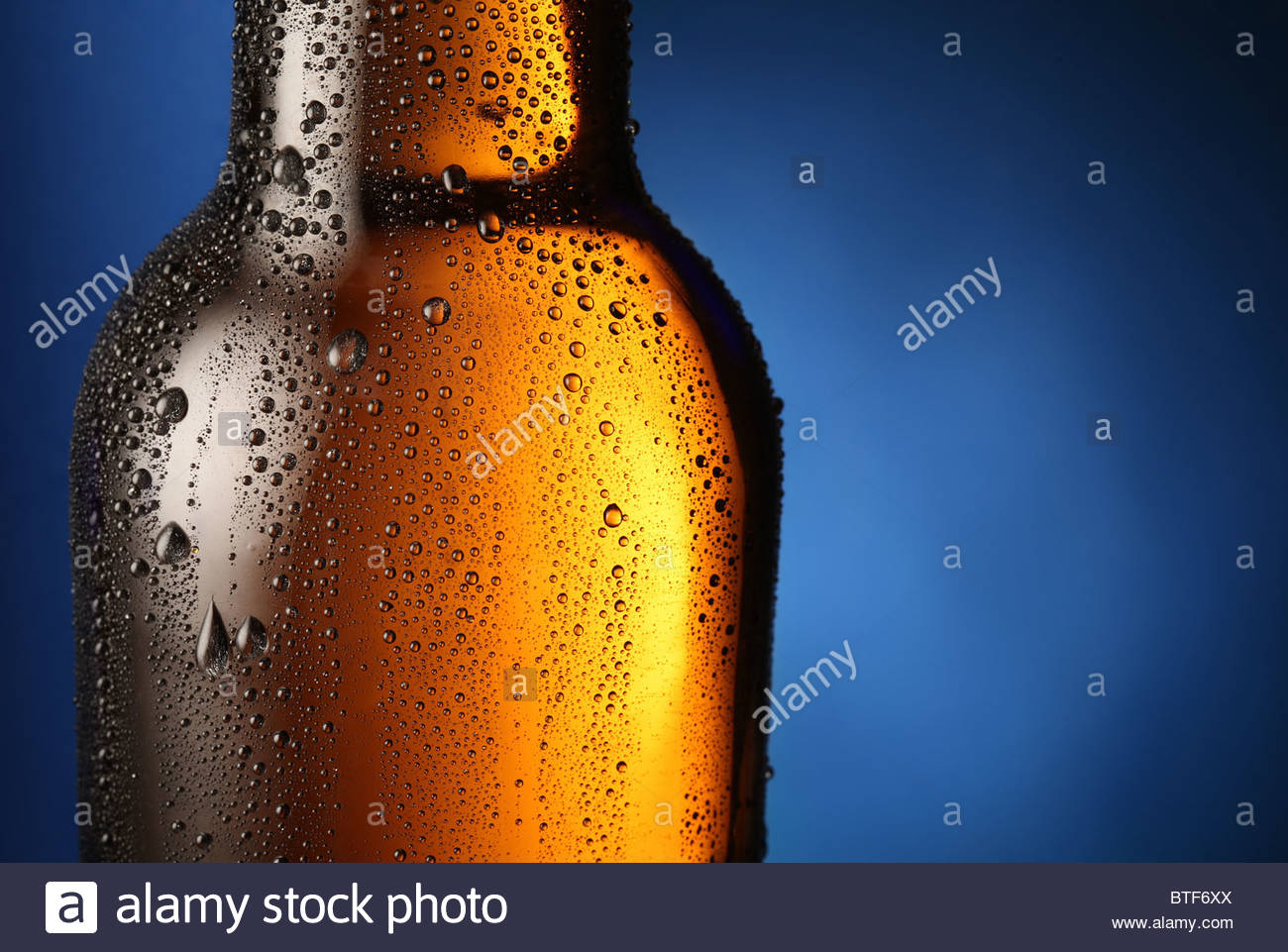 Bottle of beer with drops on a blue background Close up part of 1300x961