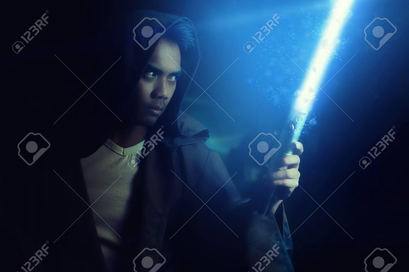 Young Warrior Holding A Lightsaber On A Dark Background Stock 1300x866
