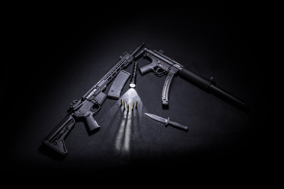 Two Black Assault Rifle Beside Tactical Knife Bullets And Torch 975x650