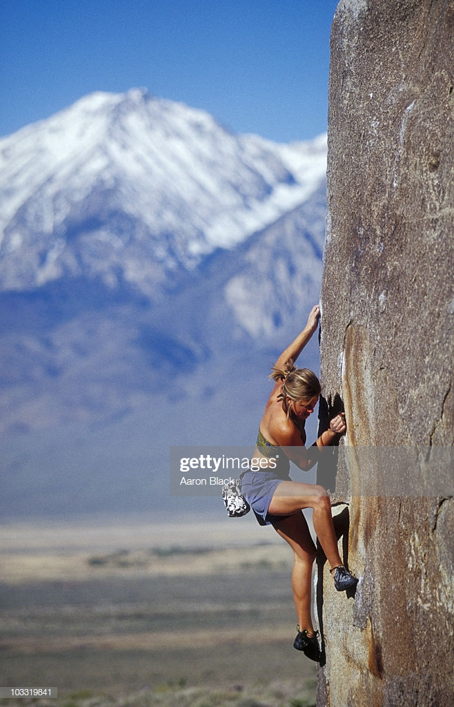 Young Woman Bouldering In Sun With Snow Capped Mountain Background 658x1024