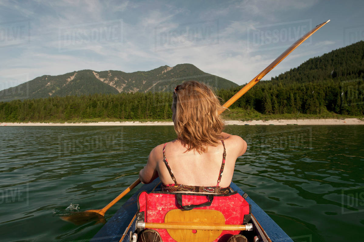 Rear view of woman paddling a canoe with mountain range in 1200x798