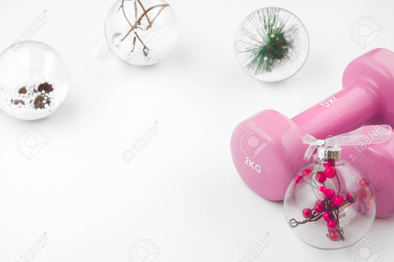 Pink Dumbbells And Christmas Ornaments Decoration On White 1300x866