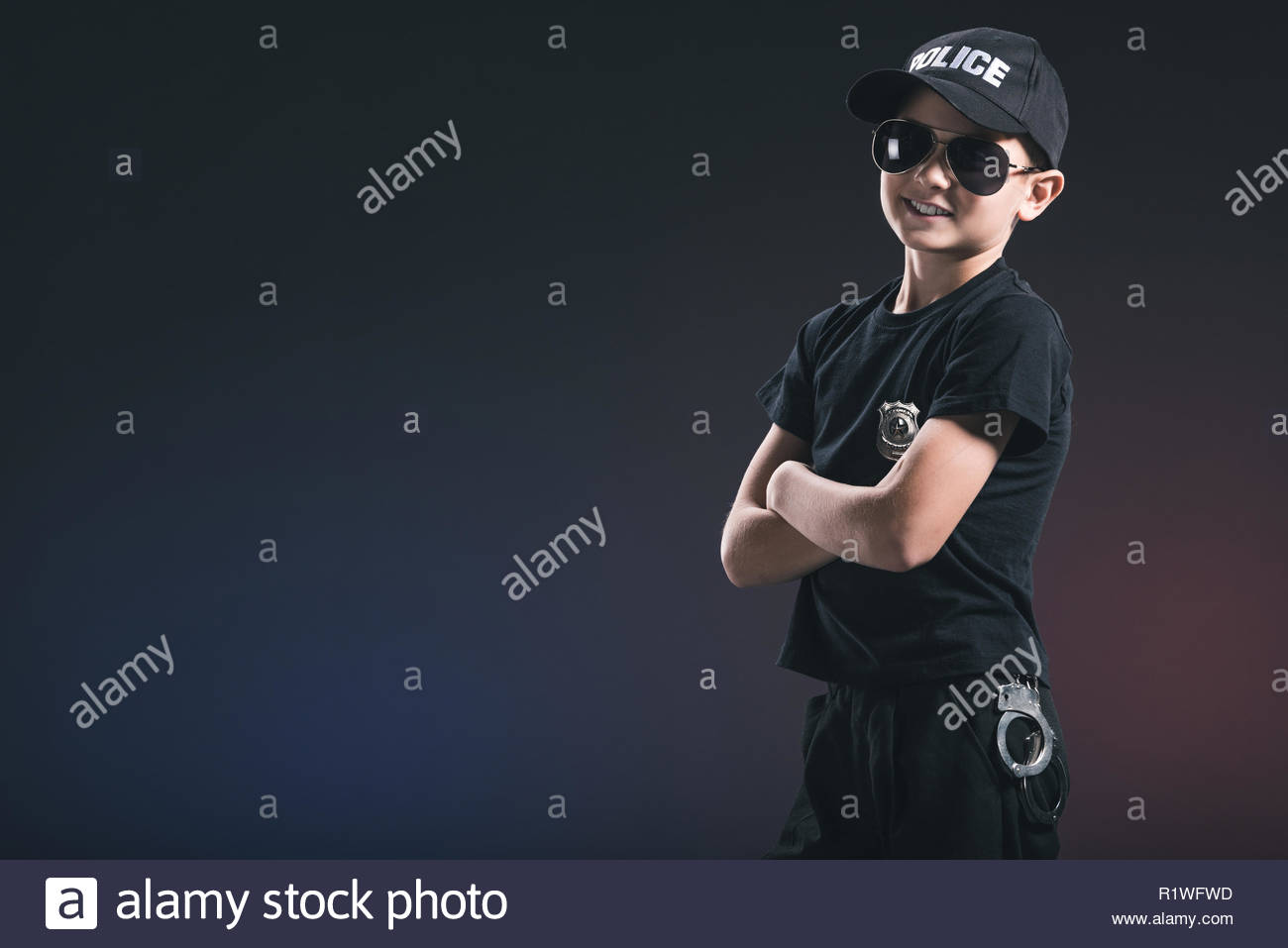 portrait of smiling boy in policeman uniform and sunglasses on 1300x957