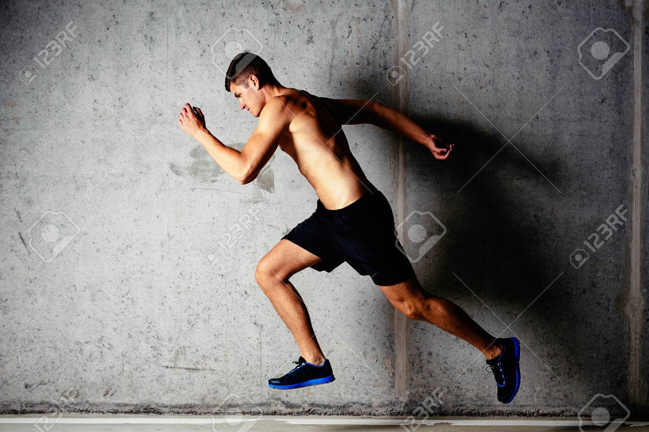Photo Of A Running Muscular Sportsman On A Concrete Background 1300x866