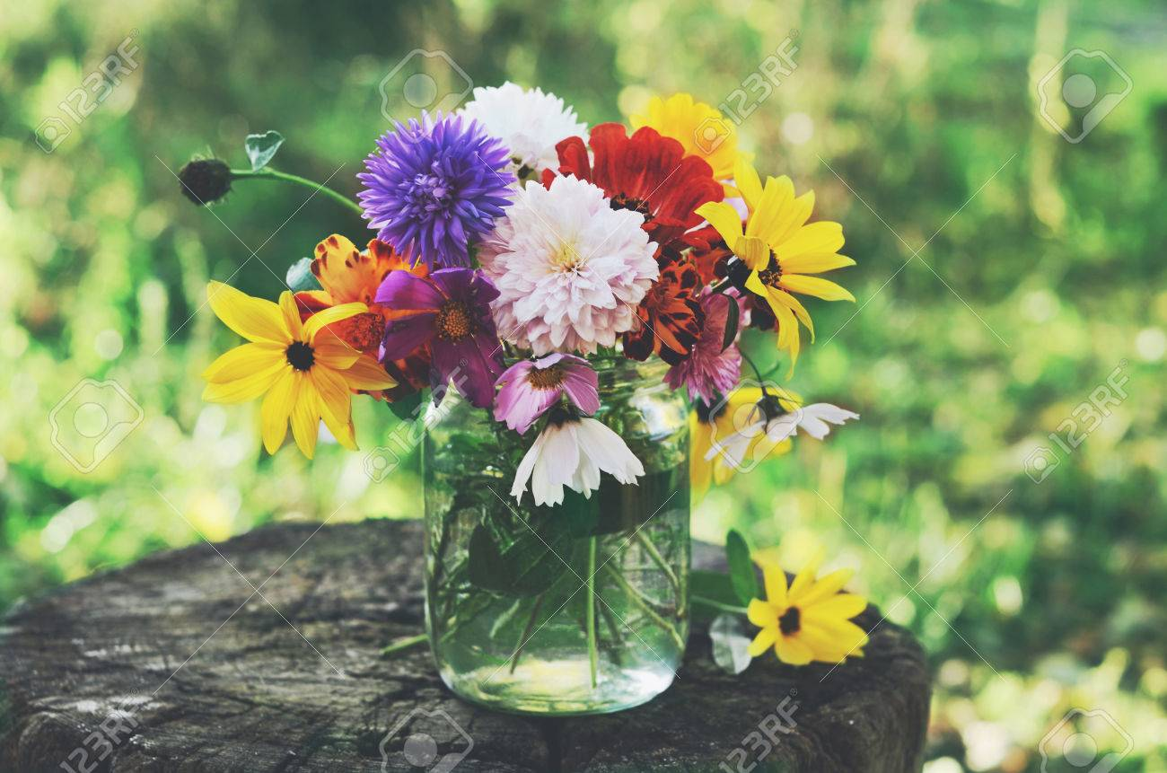 Bunch Of Flowers In Glass Jar On Tree Stub Summer Background 1300x861