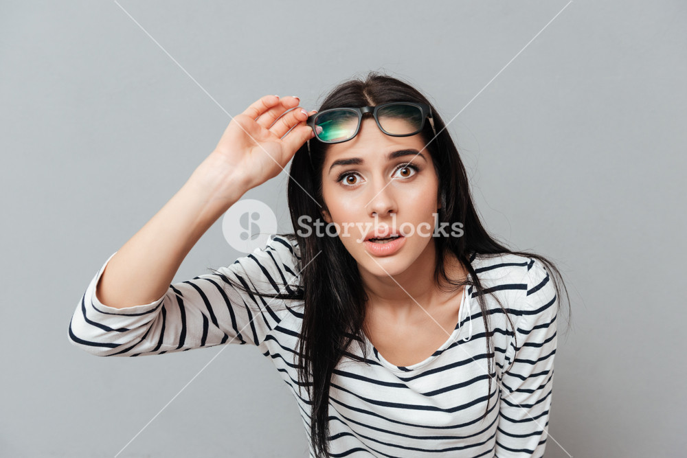 Young woman wearing eyeglasses shocked over grey background 1000x667