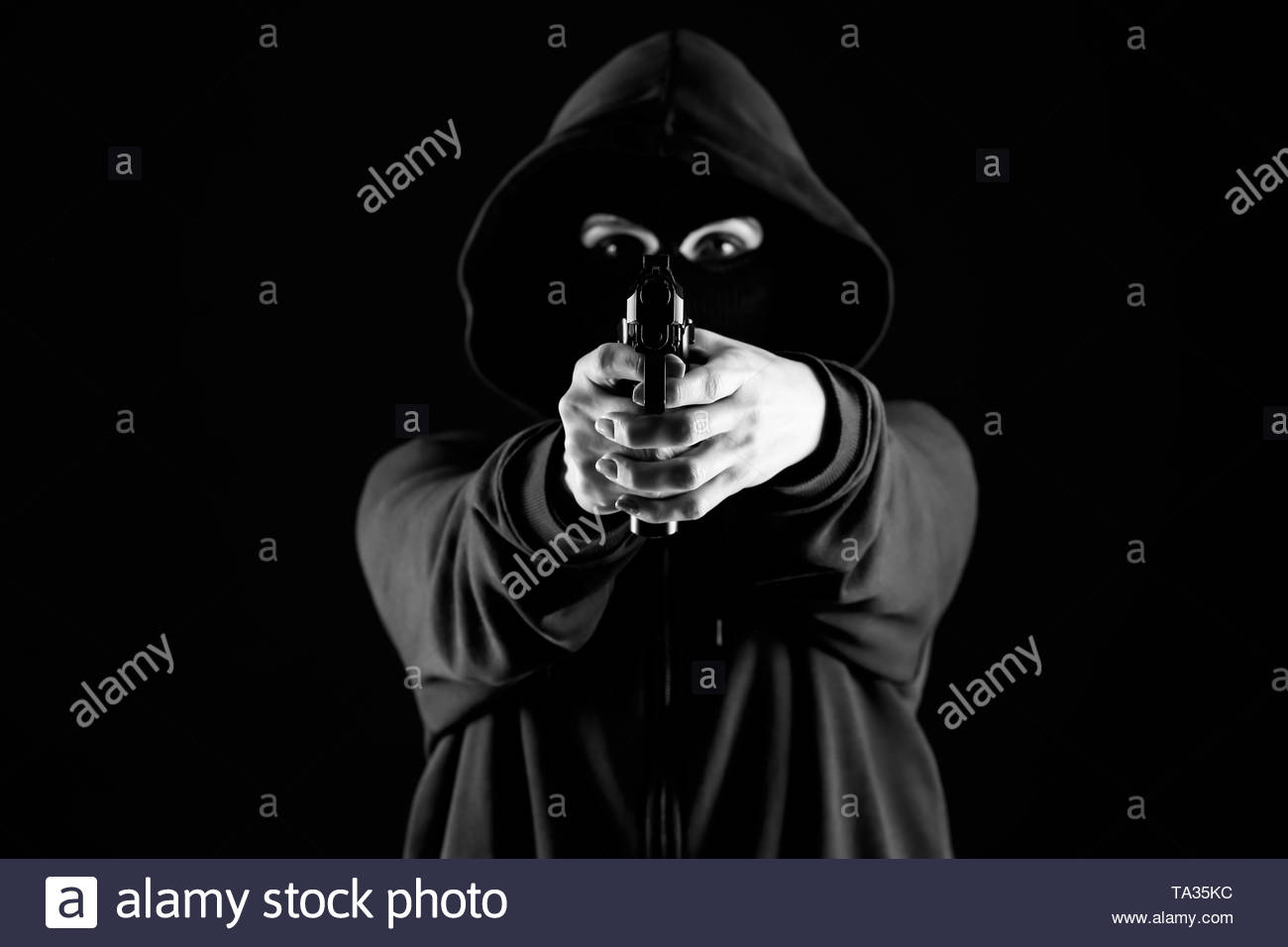 Bandit with gun aiming at viewer on dark background Stock Photo 1300x956