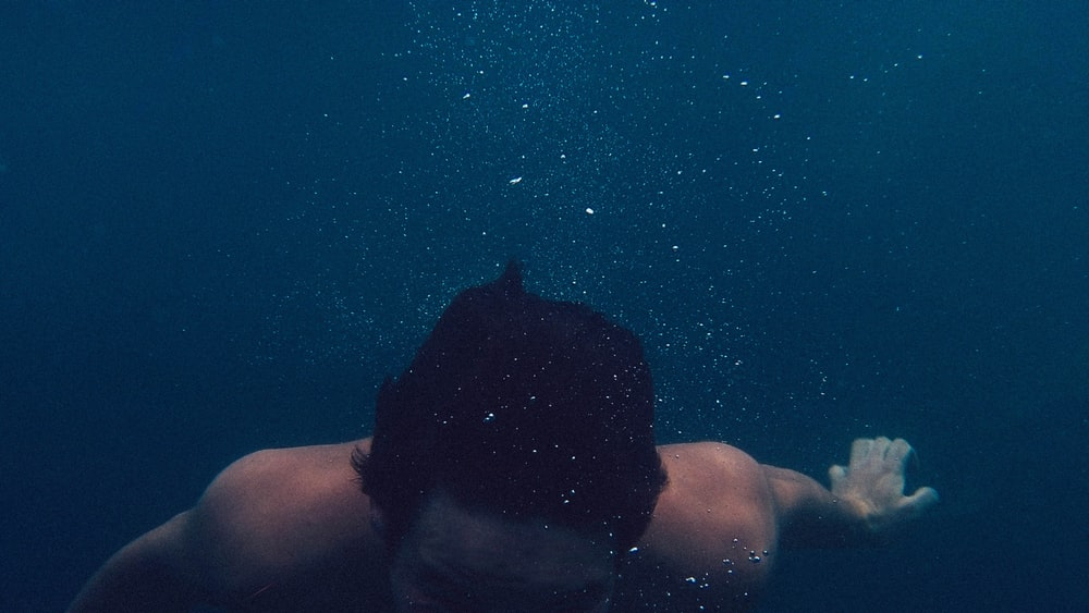 man submerged on body of water photo Water Image on Unsplash 1000x563