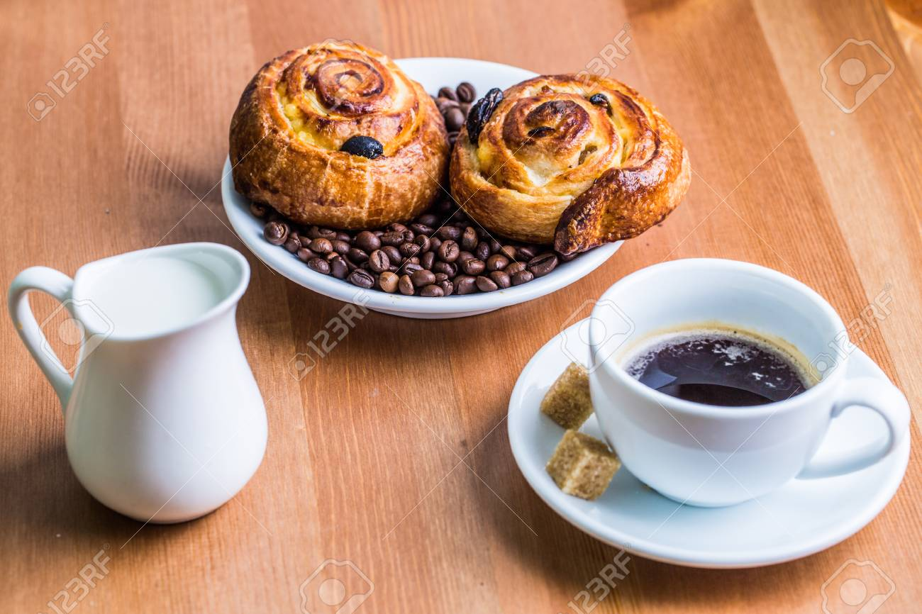 Coffee Cup With Cinnabon And Milk Jug On Wooden Background 1300x866