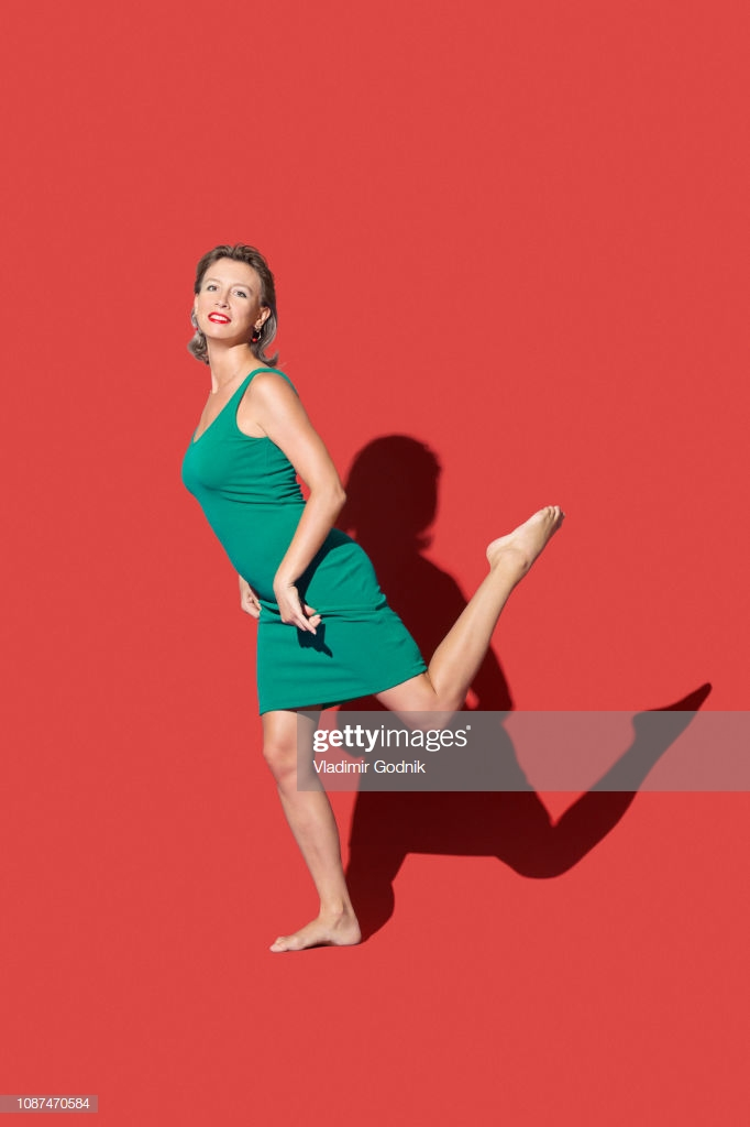 Portrait Confident Barefoot Woman On Red Background High Res Stock 682x1024