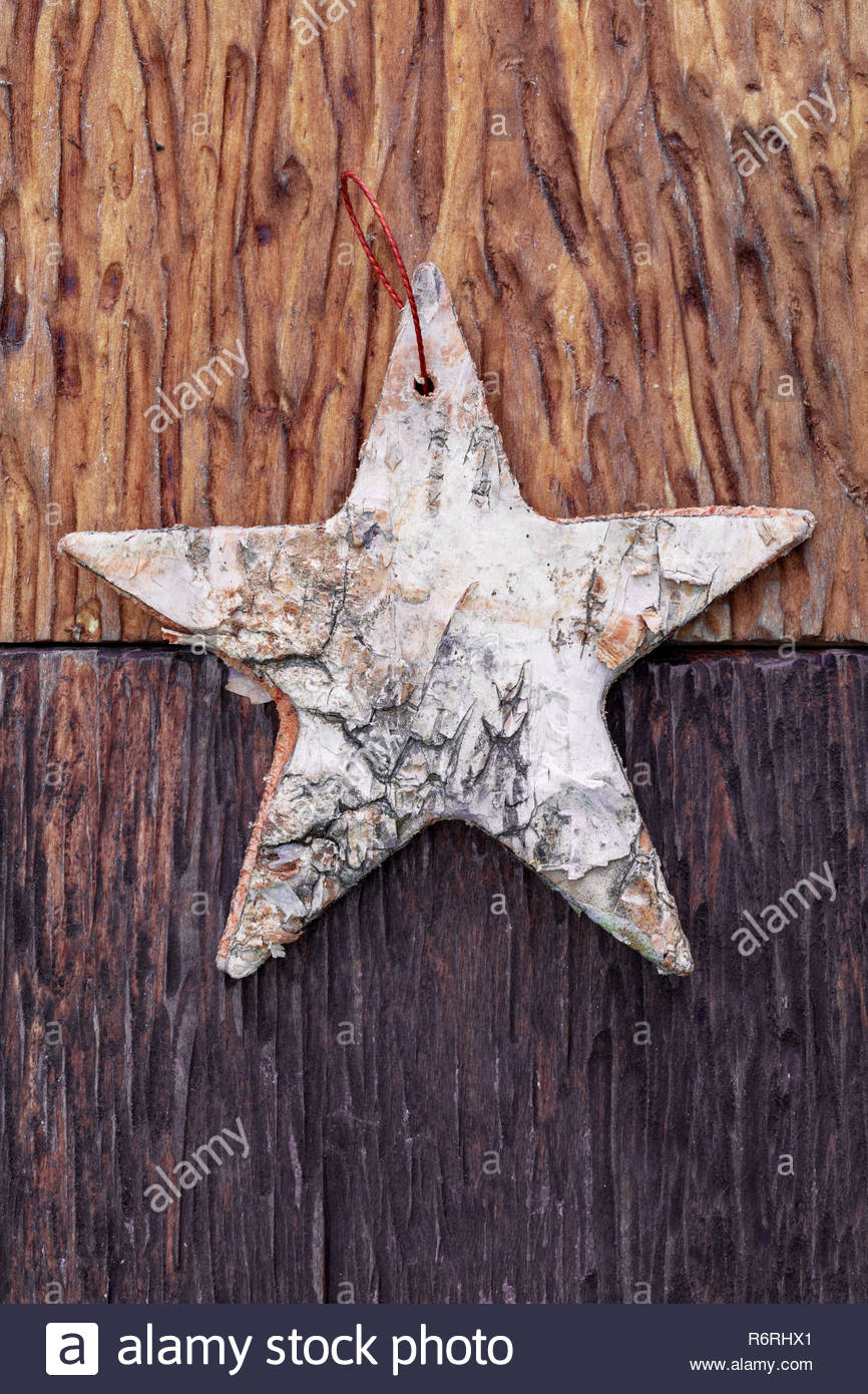 Beautiful star of birch bark on wooden craftsman background light 866x1390