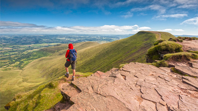 Walker at Corn Du summit overlooking Pen y Fan South Wales 642x361