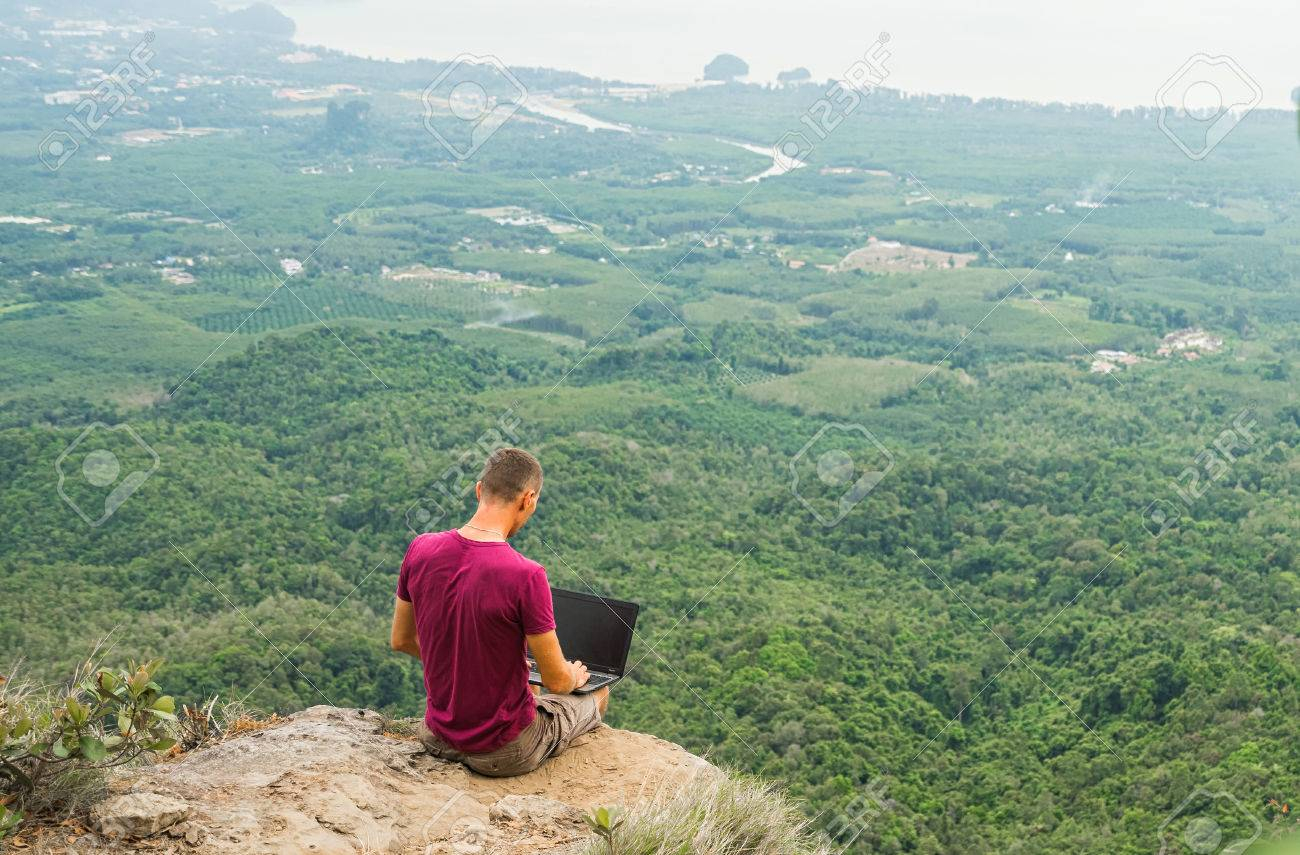 Man Working With Laptop Sitting On The Rocky Mountain On Beautiful 1300x855