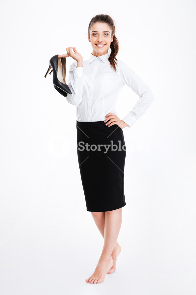 Smiling lovely young businesswoman standing barefoot and holding 667x1000