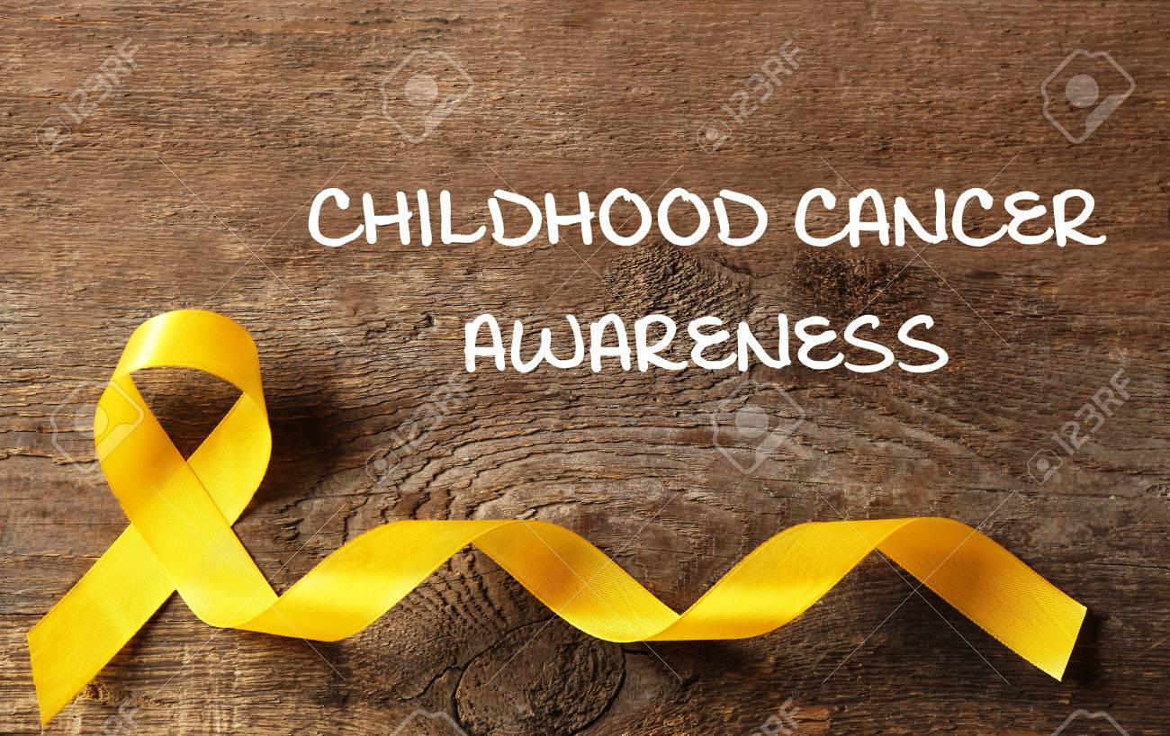 Yellow Ribbon And Text Childhood Cancer Awareness On Wooden 1300x818