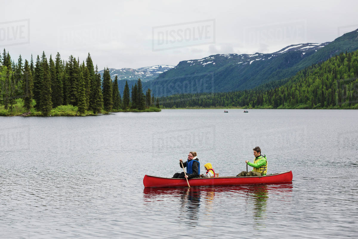 Family in red canoe on Byers Lake with green tree covered hills 1200x800