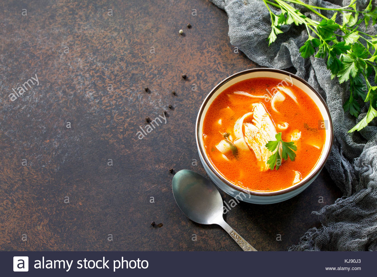 Tomato soup with pasta and chicken in a bowl on a dark stone Stock 1300x956