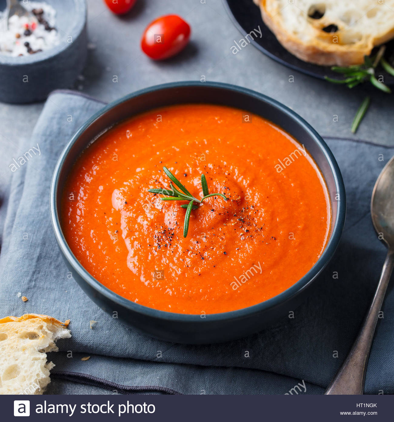 Tomato soup in a black bowl on grey stone background Stock Photo 1300x1390