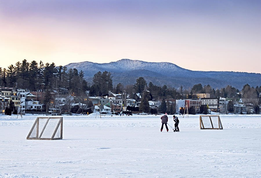 Kids Playing Hockey On Mirror Lake With Lake Placid Village Shown 900x614