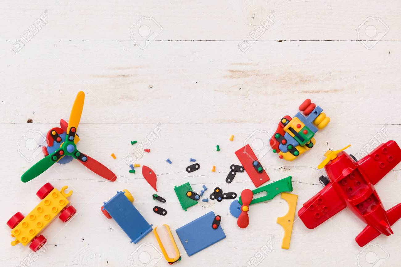 Top View On Colorful Toy Bricks On A White Wooden Background 1300x866
