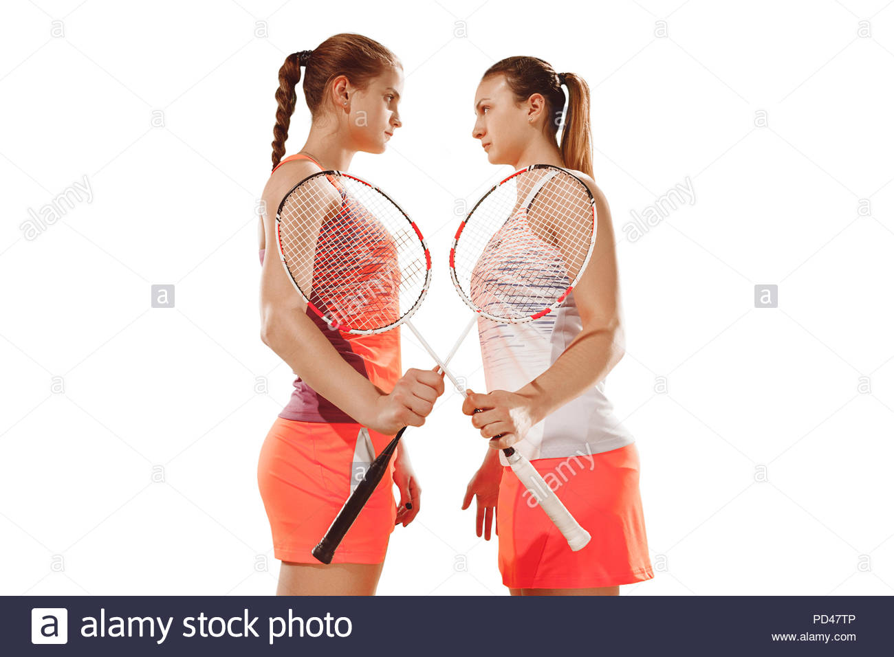 Young women before playing badminton standing over white studio 1300x956