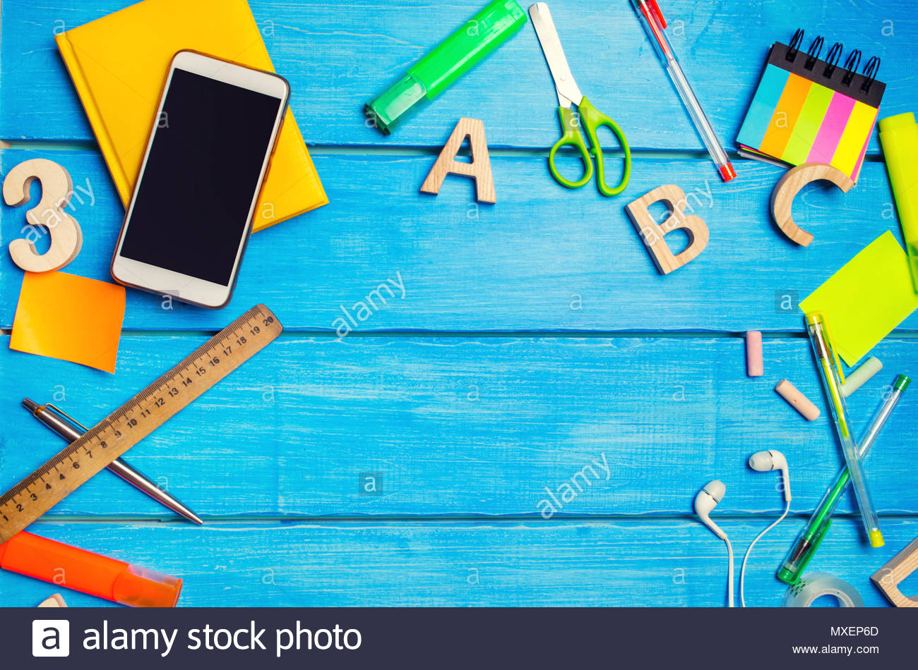 A pile of school supplies on a blue wooden table background The 1300x950