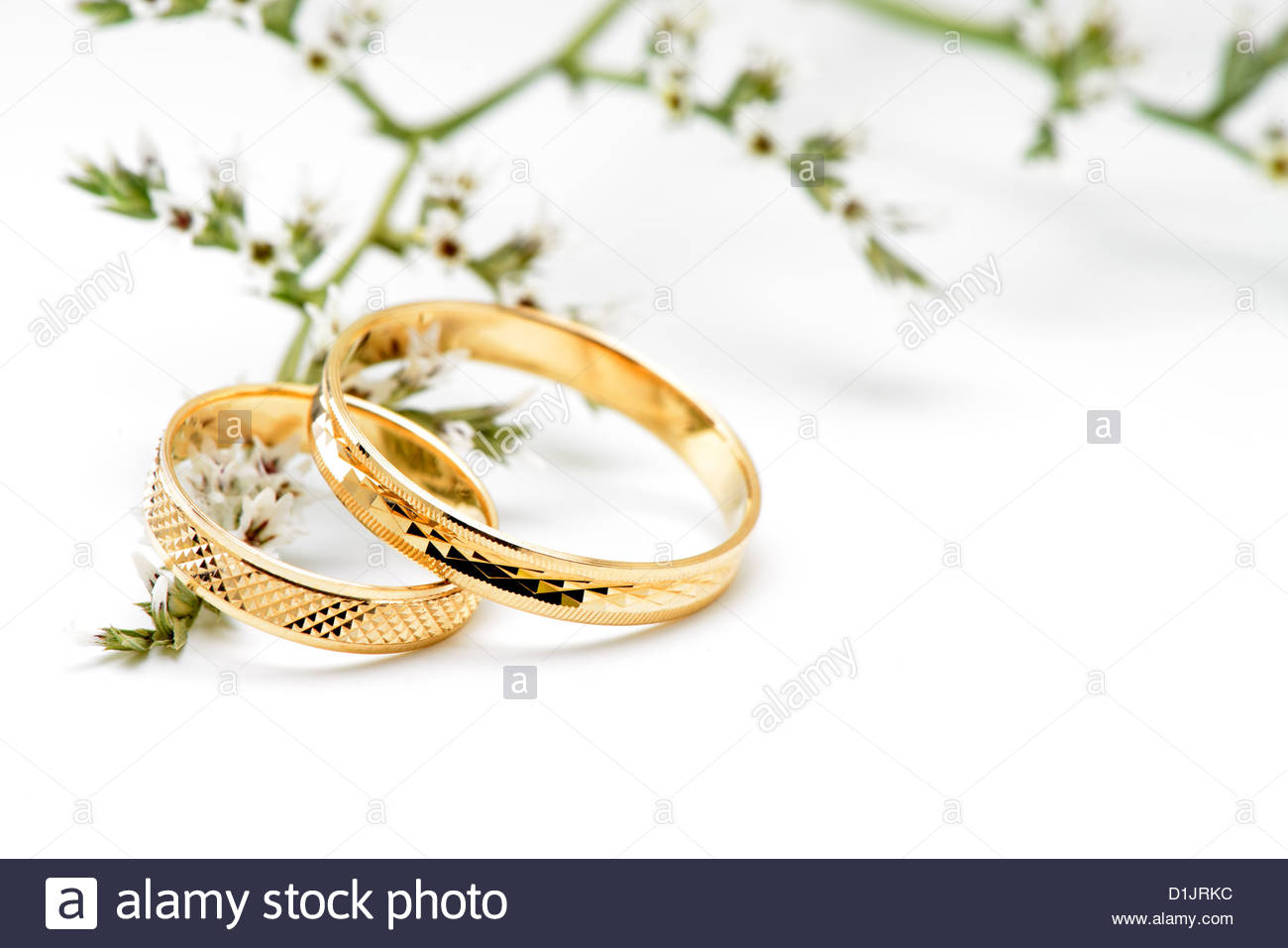 Gold wedding rings and branch flowers Isolated on white 1300x957