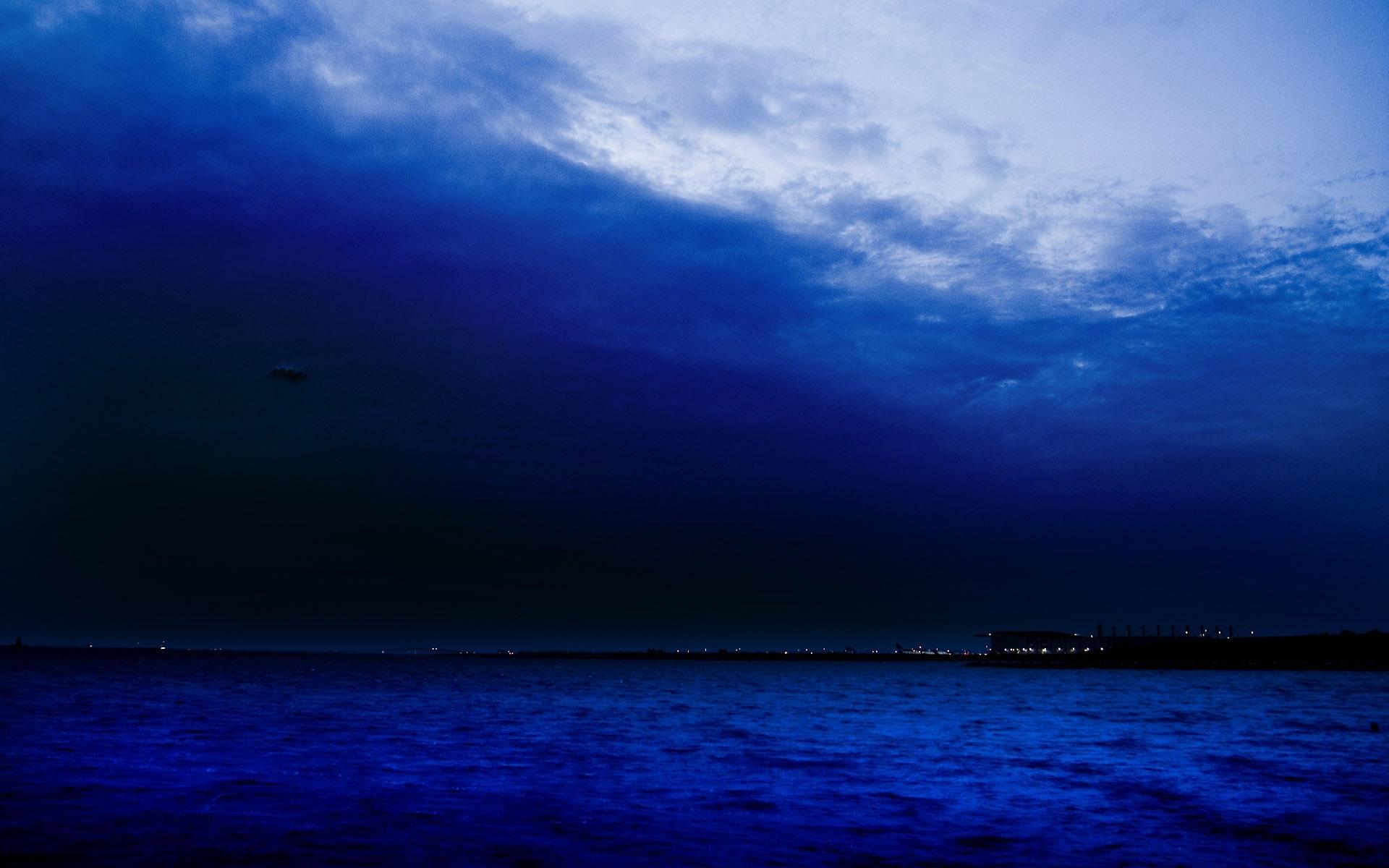 sea ocean coast shore night lights sky clouds wallpaper background 1920x1200