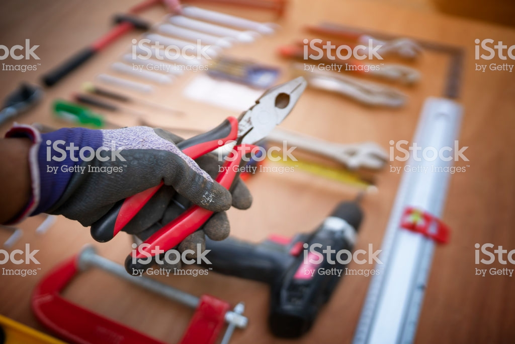 Hand Holding Pliers With Craftsman Tool Background Stock Photo 1024x683
