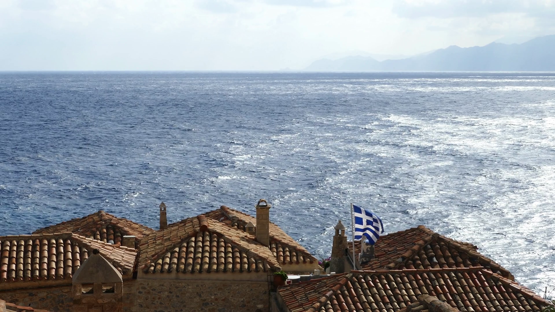 Greek flag on the roof in the village Monemvasia Greece Stock 1920x1080
