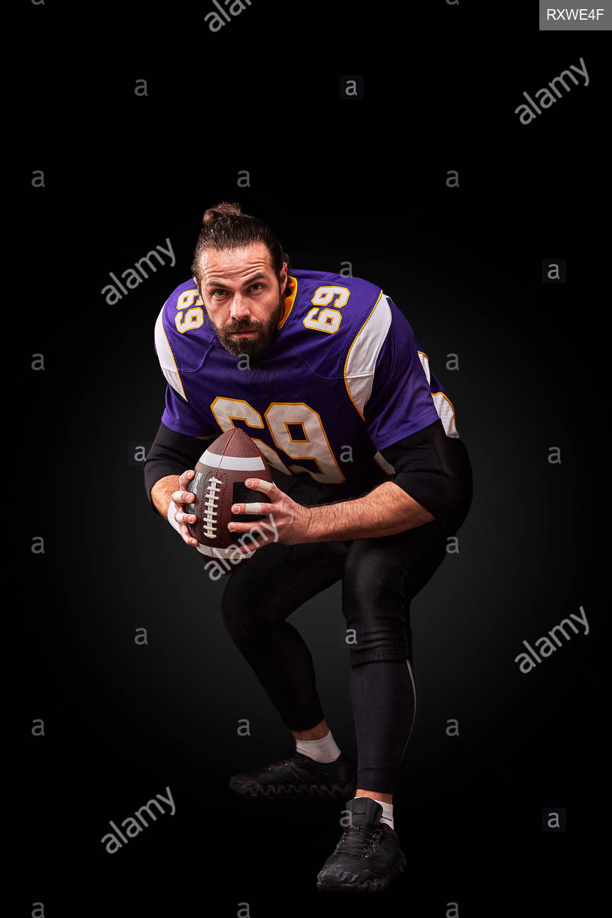 Portrait of American football player throwing ball over black 867x1300