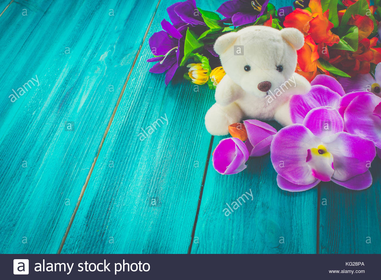 Mishka Teddy and artificial flowers on a blue wooden background 1300x956