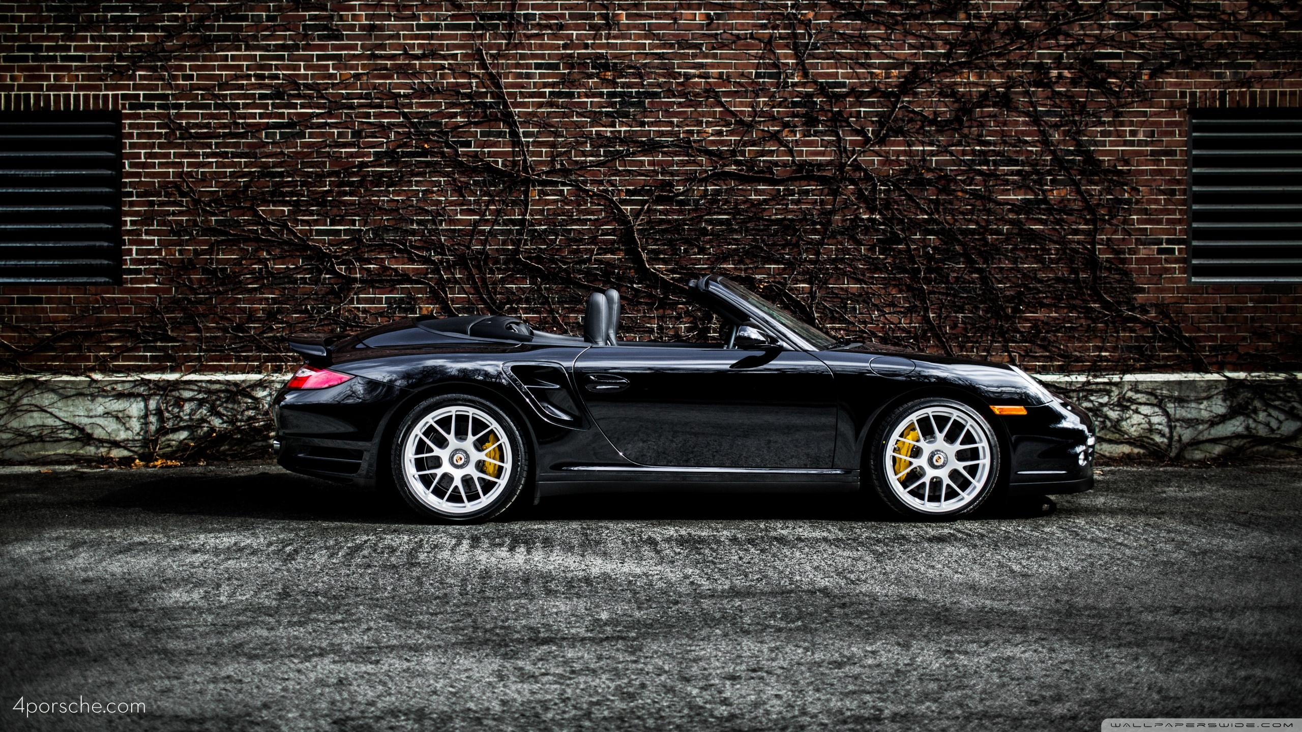 Black 2012 Porsche 911 997 Turbo S Cabriolet by a brick wall 2560x1440